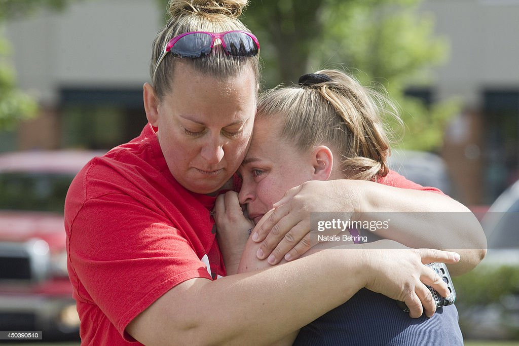 Parents of Reynolds High School students console one another in a nearby parking lot after word of a school shooting June 10, 2014 in Troutdale, Oregon. Authorities said one student was fatally shot and the gunman was found dead at an Oregon high school.