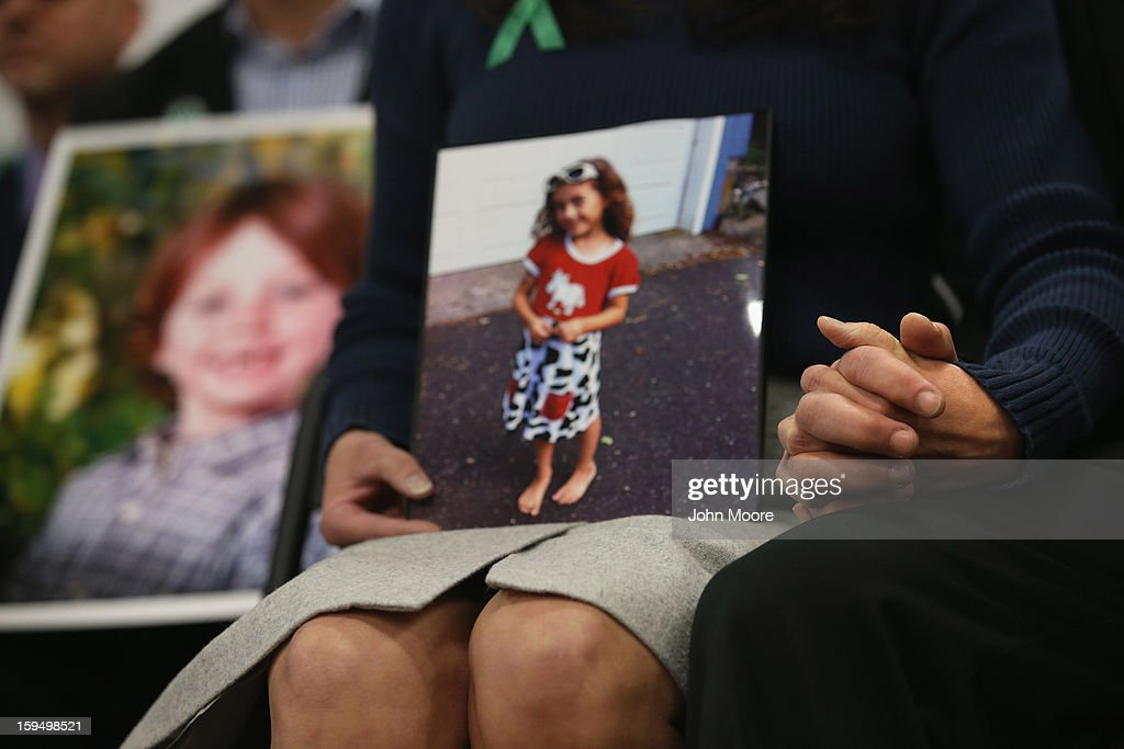 Parents of Sandy Hook Elementary massacre victims hold hands during a press conference on the one month anniversary of the Newtown elementary school massacre on January 14, 2013 in Newtown, Connecticut. Eleven families of Sandy Hook massacre victims came to the event one month after the shooting to give their support to Sandy Hook Promise, a new non-profit with the goal of preventing such tragedies in the future.