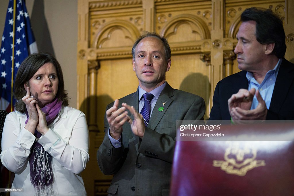 Parents of Sandy Hook School shooting victims (L to R) Jackie Barden, Mark Barden, and Neil Heslin, applaud before the signing of a gun-control bill at the Connecticut Capitol on April 4, 2013 in Hartford, Connecticut. After more than 13 hours of debate, the Connecticut General Assembly approved the gun-control bill early April 4, that proponents see as the toughest-in-the-nation response to the Demember 14, 2012 Newtown school shootings.