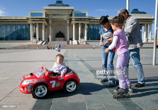 Parents paid a fee to drive their children in remotecontrolled cars on the Sukhbaatar Square on August 20 2010 in Ulan Bator Mongolia