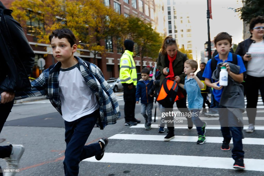 Parents pick up their children from Public School 89 near the scene where a truck plowed through a bike path in lower Manhattan on October 31, 2017 in New York City. Officials are reporting up to 8 dead and 15 people have been injured.