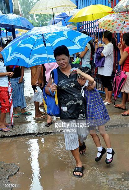Parents pick up their children wearing protective rain gear after elementary school classes in the Philippine capital Manila are called off due to...