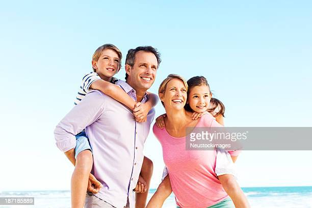 Parents Piggybacking Children Against Clear Blue Sky On Beach