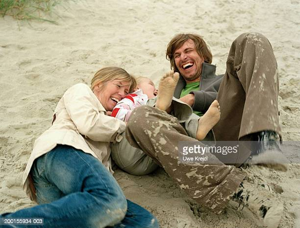 Parents play fighting with daughter (5-7) on beach, laughing