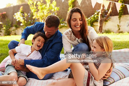 Parents Playing Game With Children On Blanket In Garden : Stock Photo