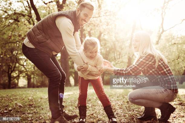 Parents playing in park with their little daughter.