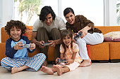 Parents playing video game with son and daughter (7-9) smiling