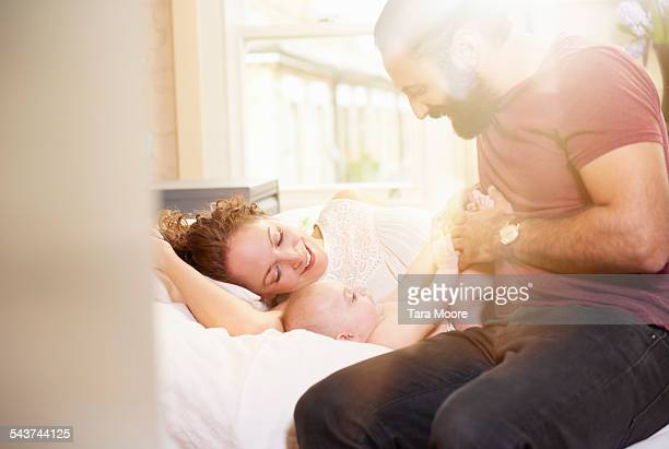 Parents playing with baby in bed at home