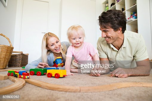Parents playing with daughter (12-23 months) at home : Stock-Foto