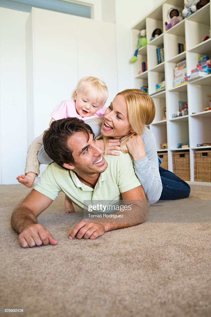 Parents playing with daughter (12-23 months) at home : Stockfoto