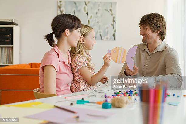 Parents with daughter (8-9) making crafts, smiling