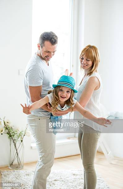 Parents playing with daughter, pretending to fly