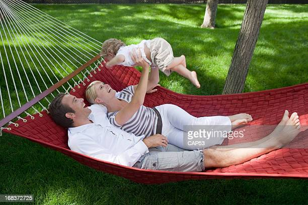 Parents Playing With Their Baby Boy In Hammock