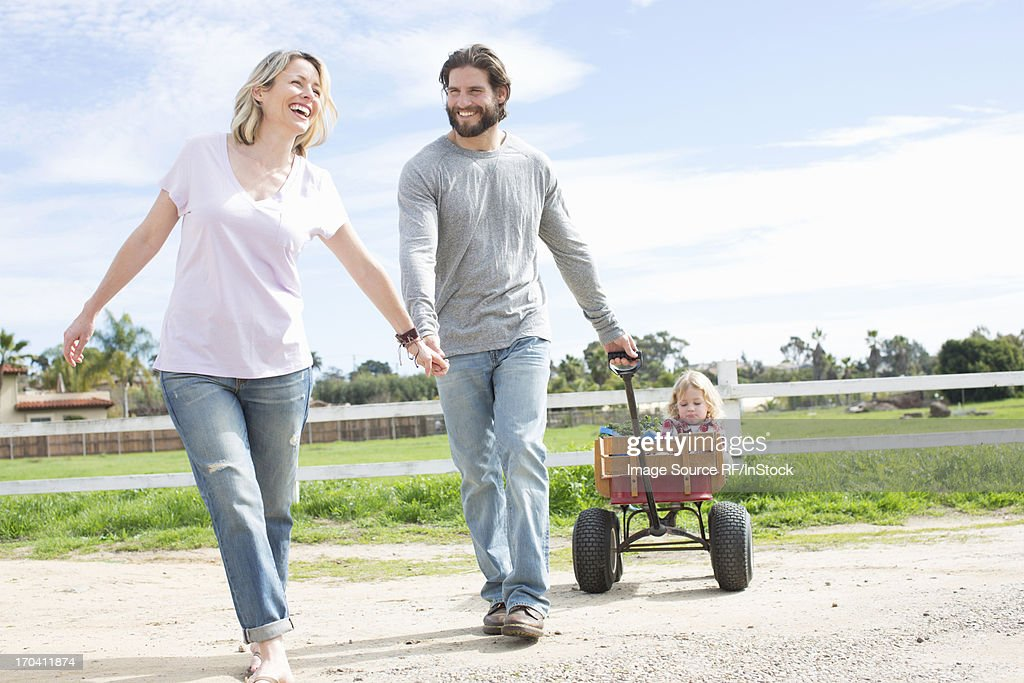 Parents pulling son in wagon : Stock Photo