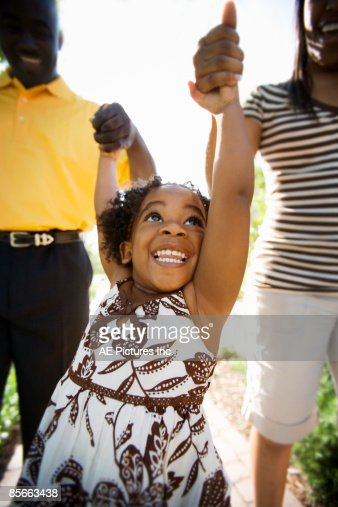 Parents raise daughter's arms up : Stock Photo
