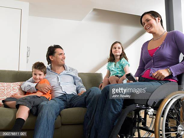 Parents relaxing in living room with son and daughter (7-9) woman in wheelchair, smiling