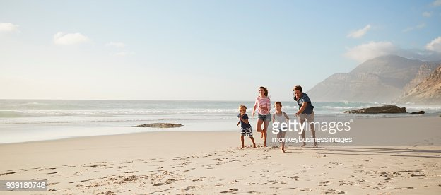 Parents Running Along Beach With Children On Summer Vacation : Foto de stock