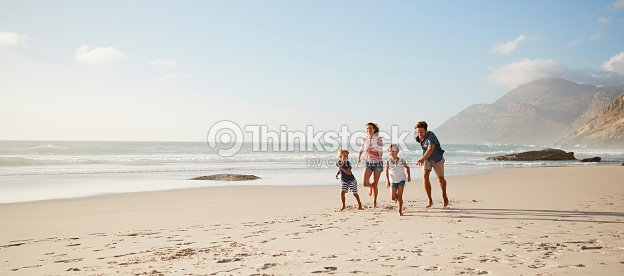 Parents Running Along Beach With Children On Summer Vacation : Stock Photo