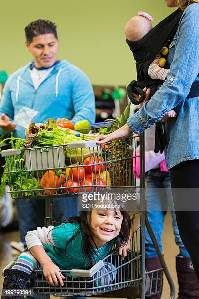 Parents shopping with children, girl in bottom of grocery cart