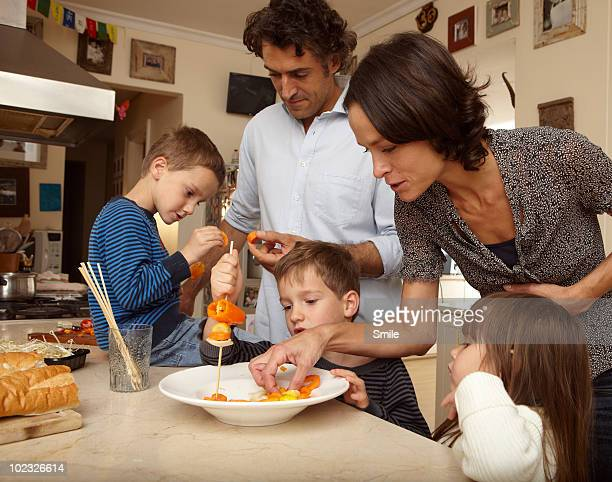 Parents showing kids how to make vegetable skewers