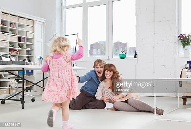 Parents sitting on floor watching their young daughter run towards them