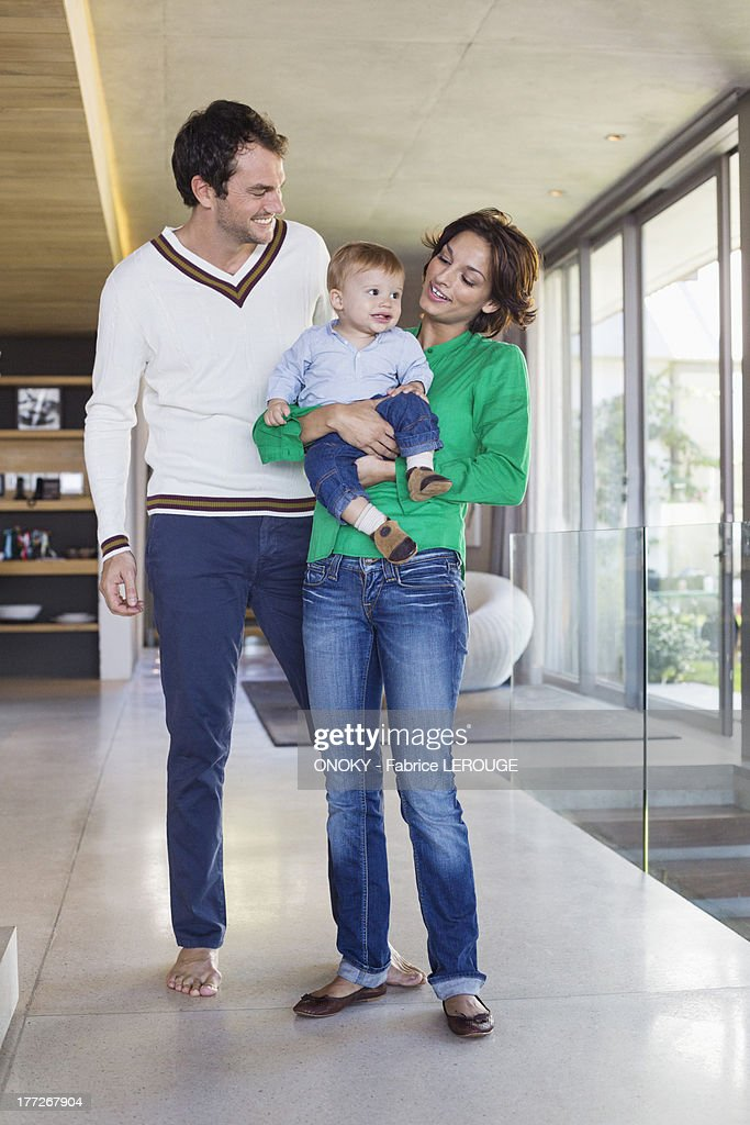 Parents smiling with their son at home : Stock Photo