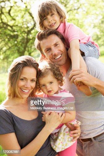Parents Standing With Children In Field Of Summer Flowers : Foto de stock