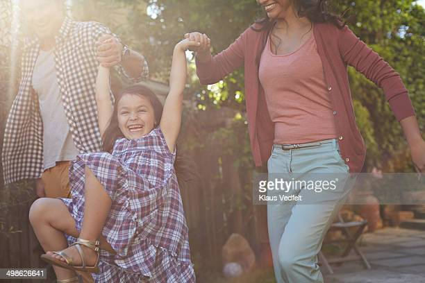Parents swinging their daughter in the garden