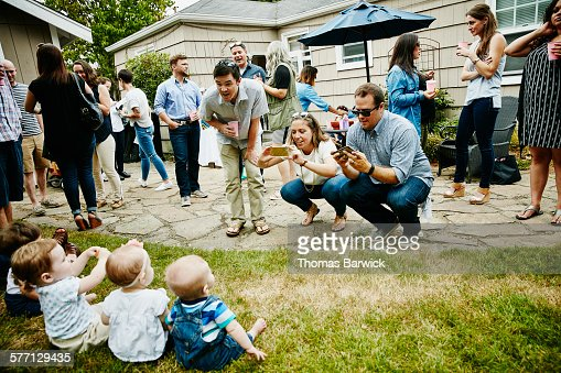 Parents taking pictures with smartphones of babies