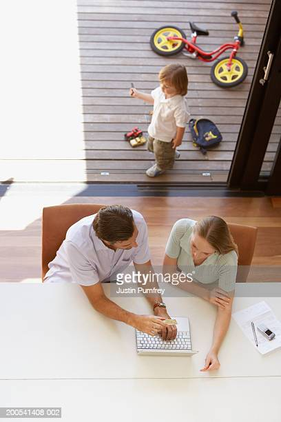 Parents using laptop, son (2-4) playing in background, overhead view