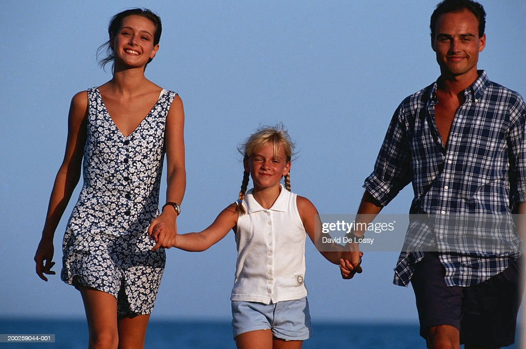 Parents walking with daughter, holding hands : Stock Photo