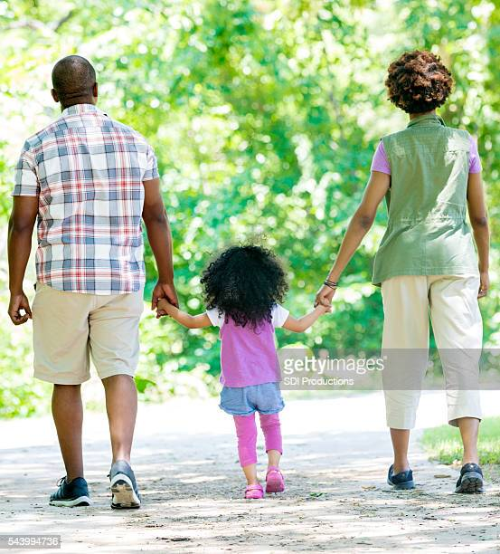 Parents walking with their daughter in park