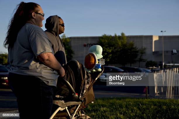 Parents watch their children on an amusement ride during the Dreamland Amusements carnival in the parking lot of the Marley Station Mall in Glen...