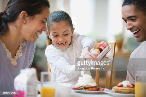 Parents watching daughter putting whipped cream on pancakes : Stock Photo