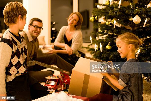 parents watching their children opening christmas presents on christmas eve