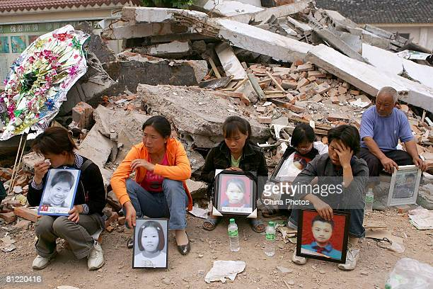 Parents who lost their children display pictures on debris of the school where the students were buried on May 23 2008 in Mianzhu of Sichuan Province...