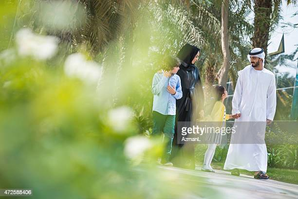 Parents with a son and daughter walking