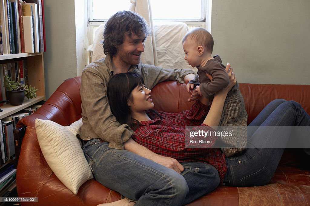 Parents with baby boy (6-11 months) sitting on sofa, smiling : Stock Photo