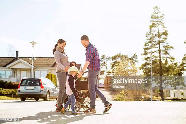 Parents with baby carriage and daughter on street