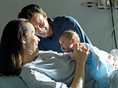 Parents with baby (0-6 months) on hospital bed