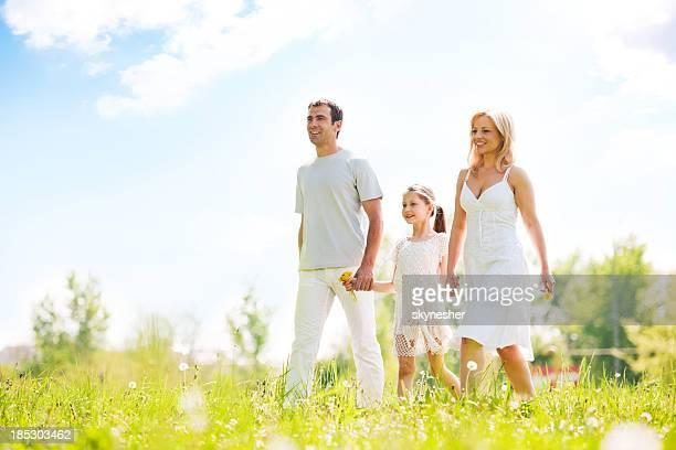 Parents with beautiful daughter walking in a park