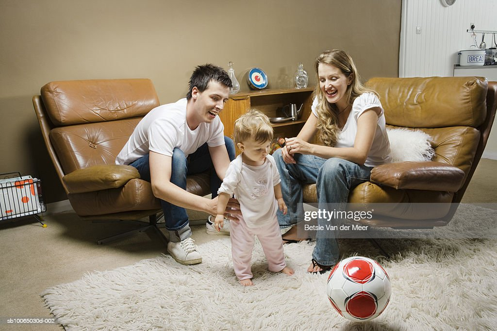 Parents with child (9-12 months) in living room, smiling