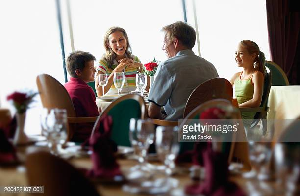 Parents with children (10-12) at table on cruise ship
