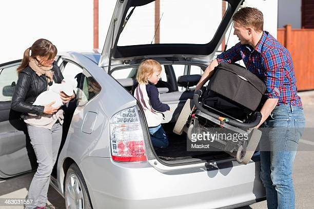 Parents with children entering into car on street