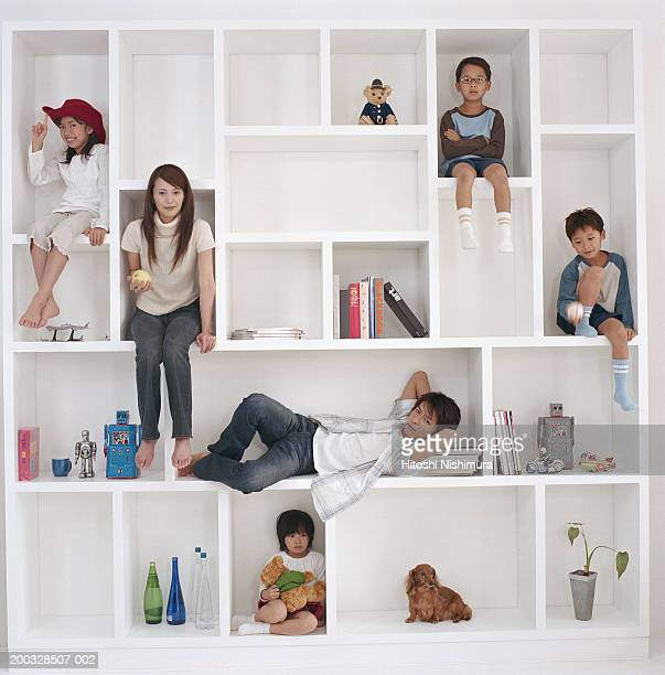 Parents with children (4-9) in cabinet of bookshelf