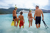 Parents with children (10-12) in water with snorkel gear, rear view