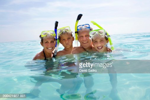 Parents with children (10-12) in water with snorkel gear smiling : Stock Photo