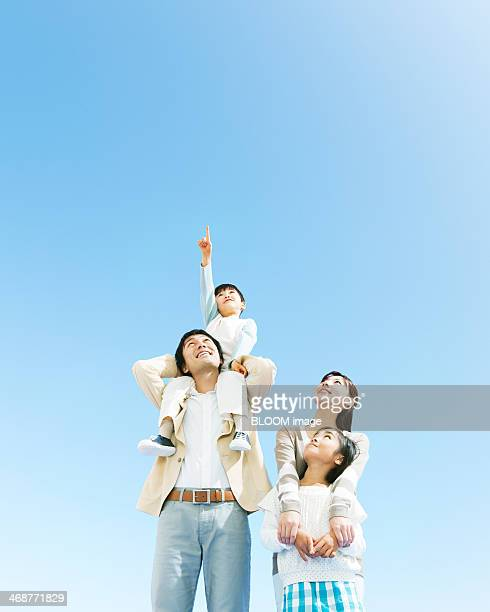 Parents With Children Looking At Sky