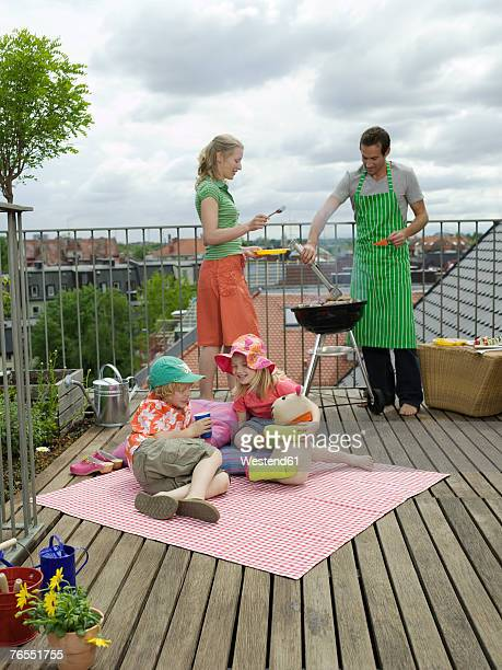 Parents with children (6-9) on balcony, man cooking on barbecue
