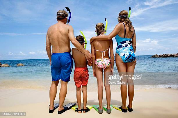 Parents with children (10-12) on beach, rear view